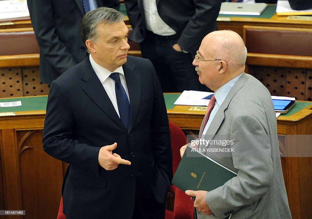 Hungarian Prime Minister Viktor Orban (L) speaks to Hungarian Foreign Minister Janos Martonyi prior to his speech in the main hall of the parliament in Budapest on February 11, 2013. AFP PHOTO / ATTILA KISBENEDEK