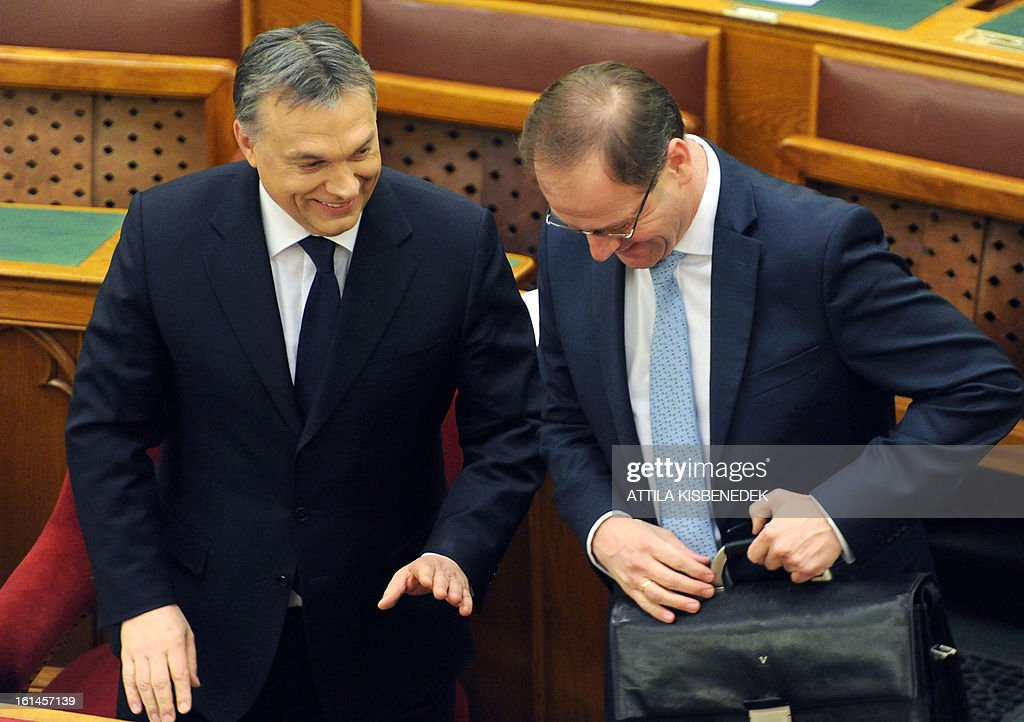 Hungarian Prime Minister Viktor Orban (L) speaks with Hungarian Minister of Public Administration and Justice Tibor Navracsics prior to his speech at the main hall of the parliament in Budapest on February 11, 2013.