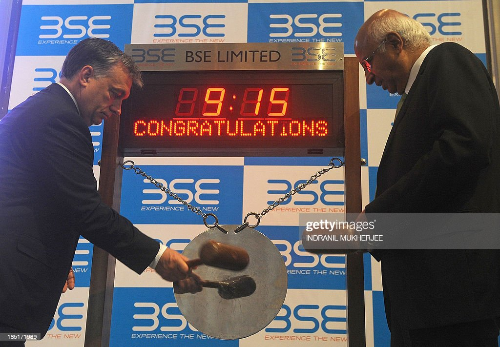 Hungarian Prime Minister Viktor Orban (L) strikes the gong to symbolically commence trading during a visit to the Bombay Stock Exchange (BSE) as BSE Chairman S. Ramadorai looks on in Mumbai on October 18, 2013. Orban is in India for a four-day state visit.