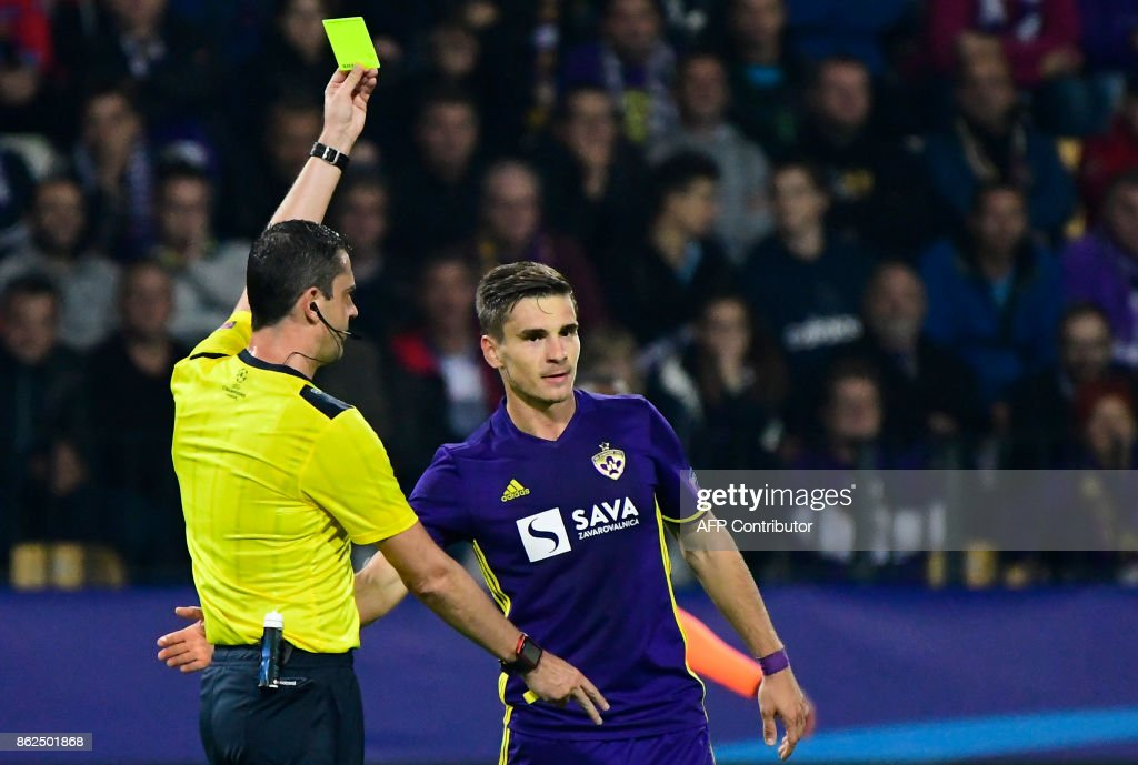 Hungarian referee Viktor Kassai (L) gives a yellow card to Maribor's Slovenian midfielder Blaz Vrhovec (R) during the UEFA Champions League group E football match between NK Maribor and Liverpool at the Ljudski vrt Stadium, in Maribor, on October 17, 2017. / AFP PHOTO / Jure MAKOVEC