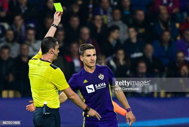 Hungarian referee Viktor Kassai gives a yellow card to Maribor's Slovenian midfielder Blaz Vrhovec during the UEFA Champions League group E football...