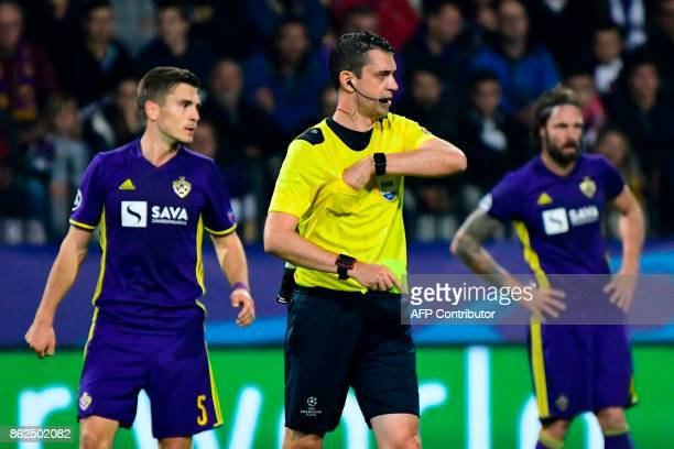 Hungarian referee Viktor Kassai reacts after giving a yellow card to Maribor's Slovenian midfielder Blaz Vrhovec during the UEFA Champions League...