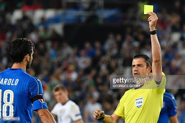 Hungarian referee Viktor Kassai show a yellow card to Italy's midfielder Marco Parolo during the Euro 2016 quarterfinal football match between...