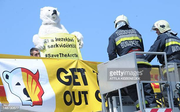 Hungarian rescue workers prepare to remove a Greenpeace activist wearing ice bear costume from the roof of a local petrol station in Budapest on July...