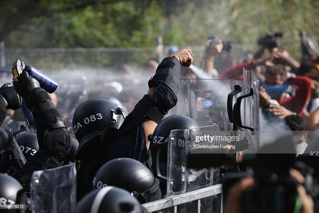 Hungarian riot police fire pepper spray and water cannons as they repel an attempt by migrants to break the border post gate and pull down the razor...