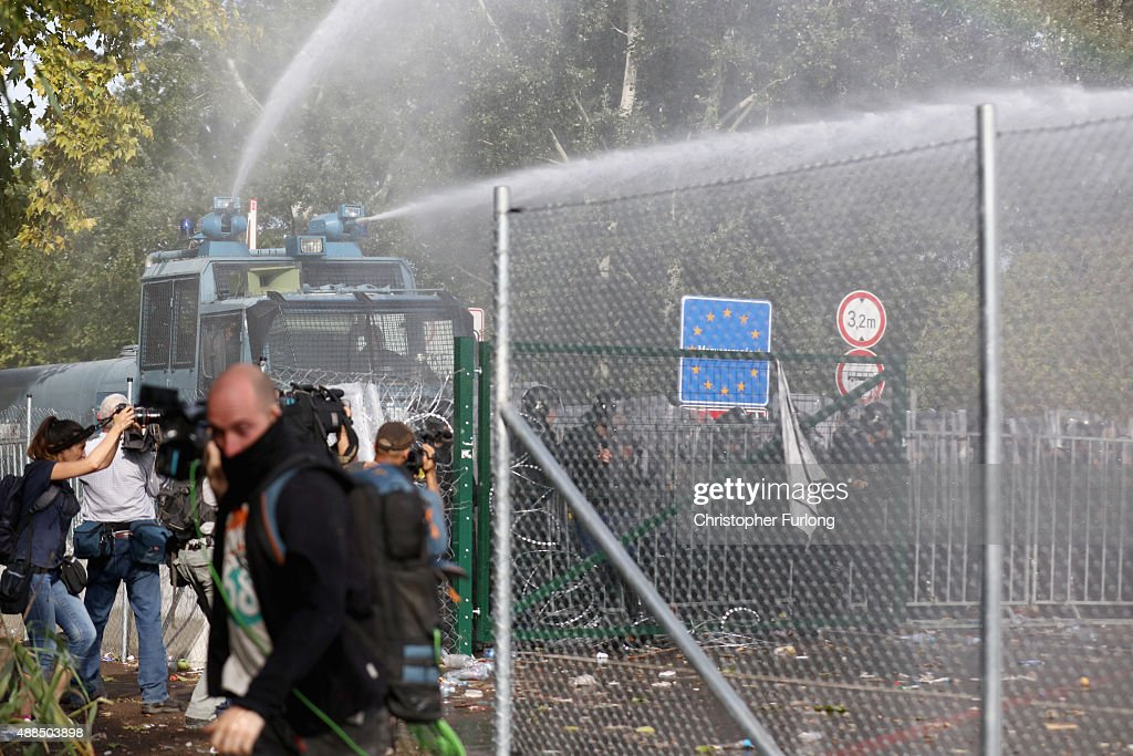 Hungarian riot police fire water cannons as they repel an attempt by migrants to break the border post gate and pull down the razor wire fence on...
