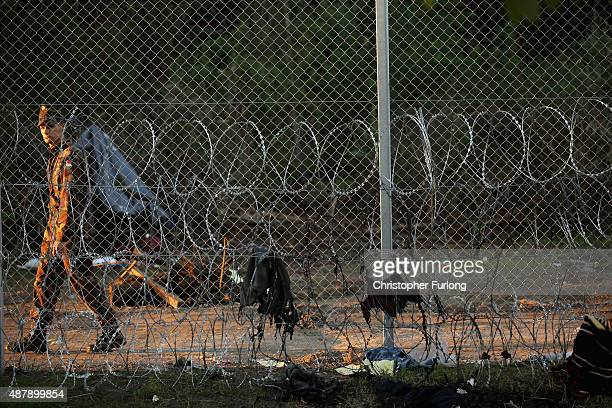 A hungarian soldier patrols the razor wire fence at the Hungarian border with Serbia on September 12 2015 in Roszke Hungary Migrants are rushing to...