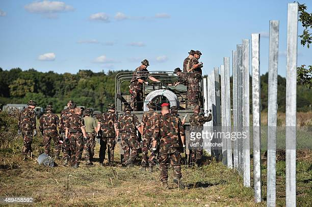 Hungarian soldiers erect a fence at a border point between Croatia and Hungary where migrants are being transported by bus through to Austria on...