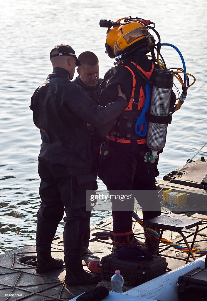 Hungarian specialist soldiers prepare a diver to dive to a bomb in the river Danube in Budapest, on October 19, 2012. 8,000 people were evacuated after the discovery of a 500-kilo (1,100-pound) unexploded bomb dating from World War II close to a railway bridge over the river Danube in Budapest .