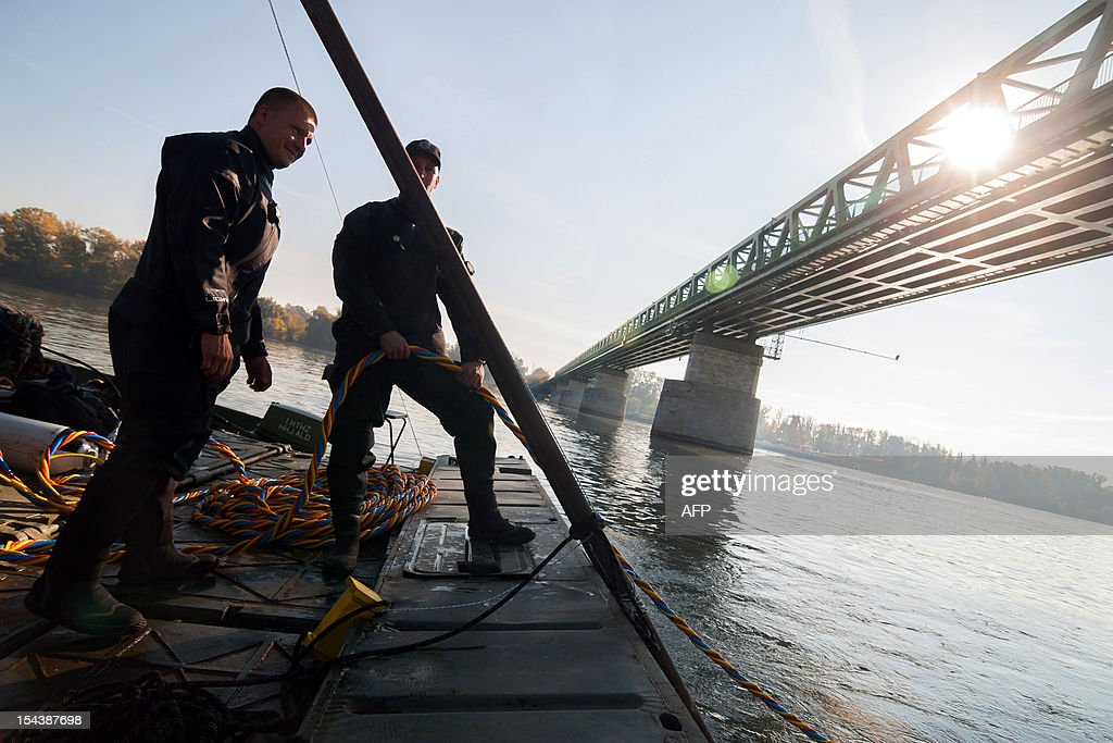 Hungarian specialist soldiers watch for a diver during a dive to a bomb in Budapest in the river Danube on October 19, 2012. 8,000 people were evacuated after the discovery of a 500-kilo (1,100-pound) unexploded bomb dating from World War II close to a railway bridge over the river Danube in Budapest .
