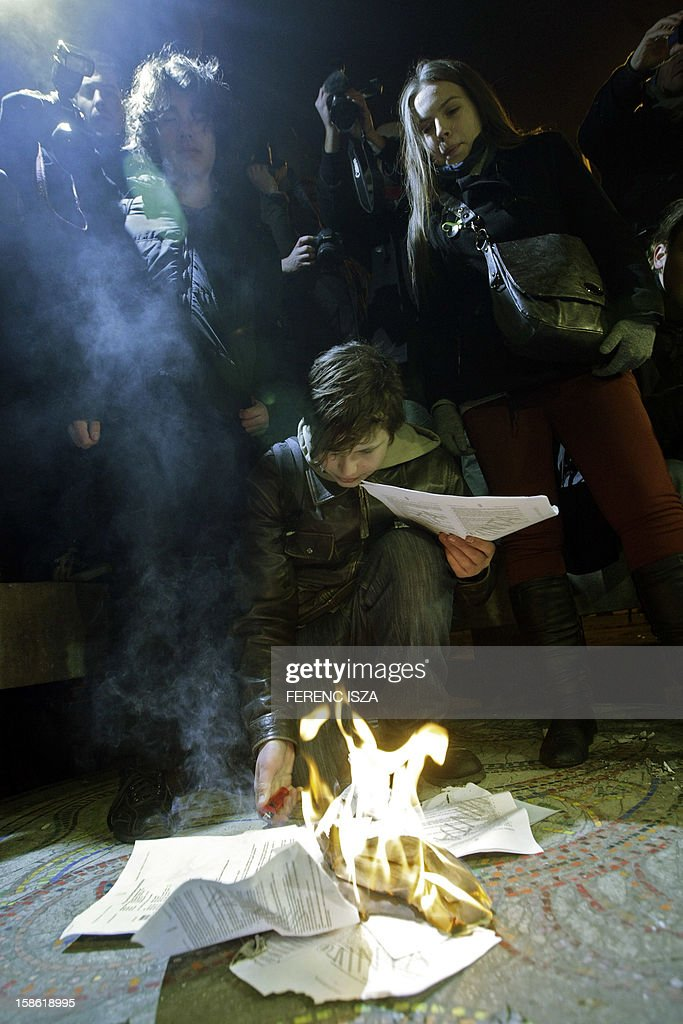 Hungarian students burn their contracts which commit students to work in Hungary after graduation in Budapest on December 21, 2012. Protests over higher education reform in Hungary spread despite government efforts to appease students angry over cuts to study grants and new rules making them promise not to move abroad after graduation. AFP PHOTO / FERENC ISZA