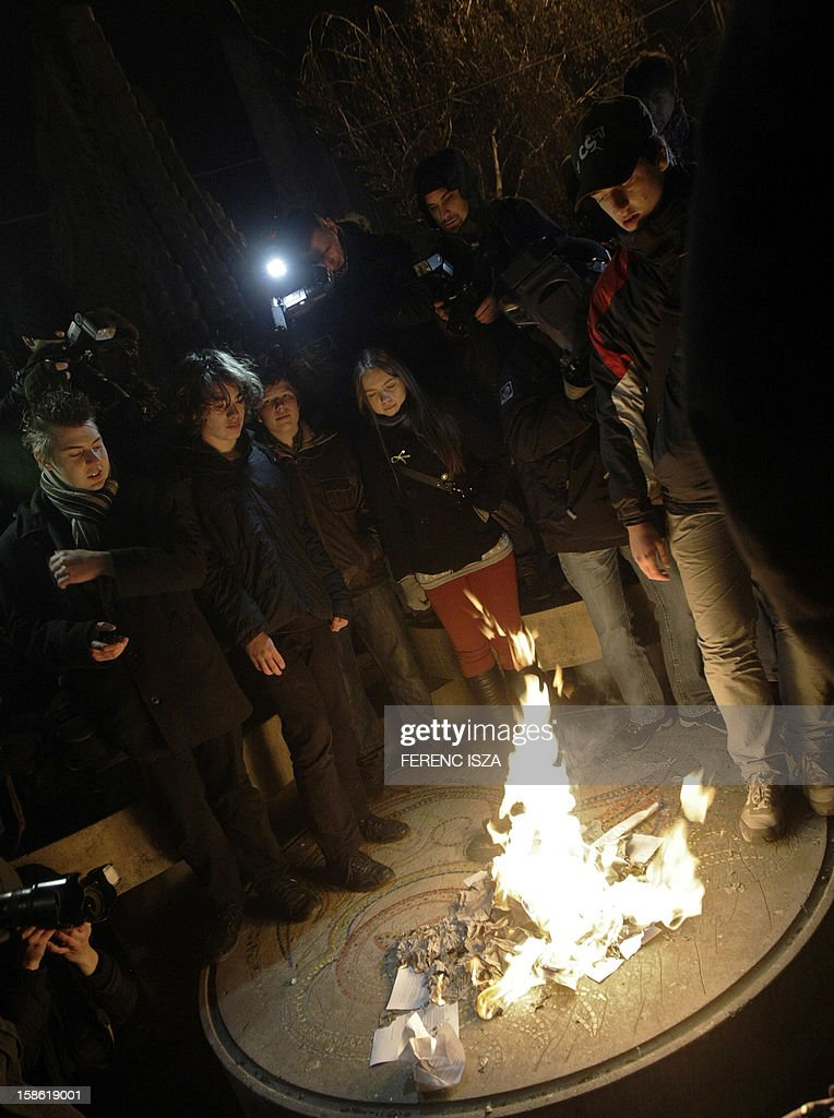 Hungarian students burn their contracts which commit students to work in Hungary after graduation in Budapest on December 21, 2012. Protests over higher education reform in Hungary spread despite government efforts to appease students angry over cuts to study grants and new rules making them promise not to move abroad after graduation.