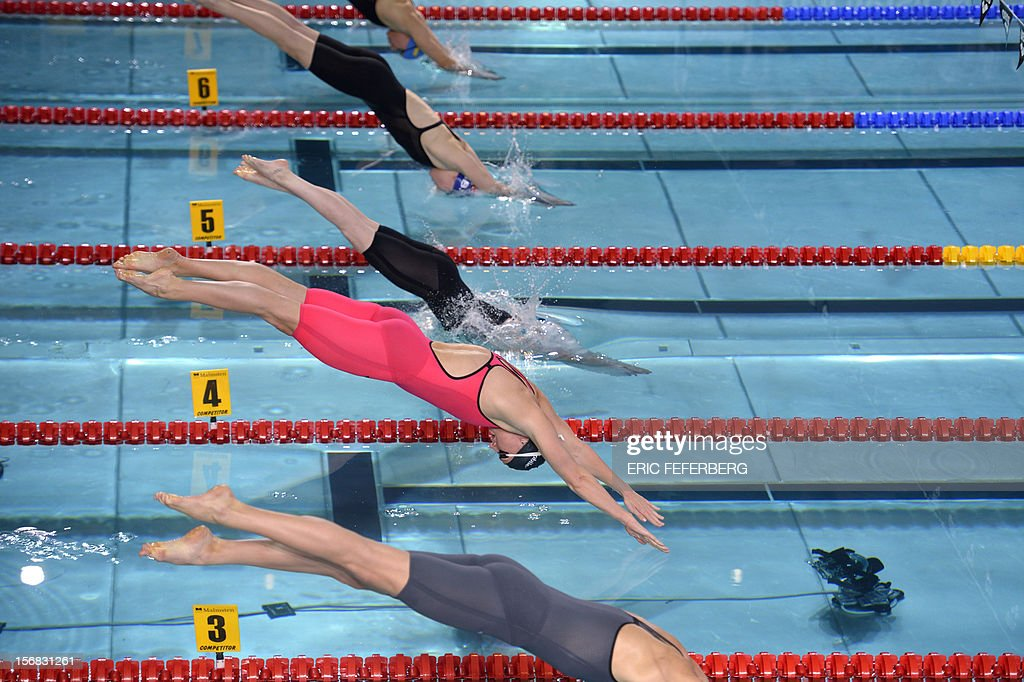 Hungarian swimmer Katinka Hosszu (pink) dives at the start of the women's 200m medley final at the European Swimming Championships on November 22, 2012, in Chartres.