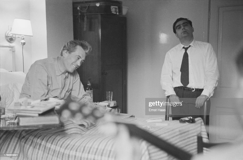 Hungarian war photographer and photojournalist Robert Capa (1913 - 1954) (right) visits American film director and screenwriter John Huston (1906 - 1987) in hospital, 1953.