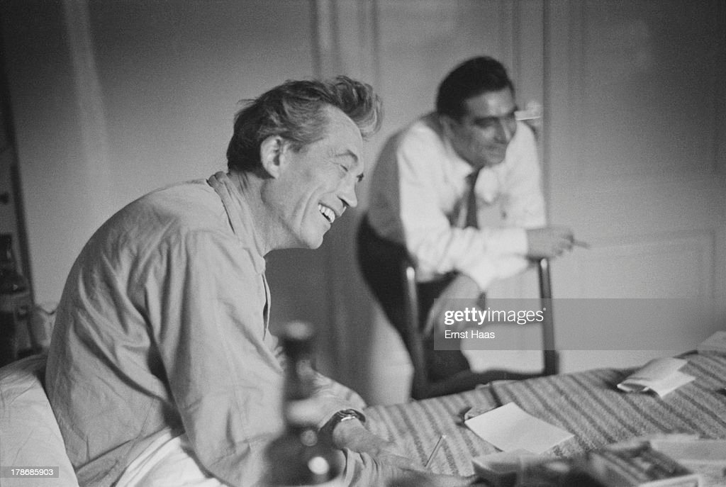 Hungarian war photographer and photojournalist Robert Capa (1913 - 1954) visits American film director and screenwriter John Huston (1906 - 1987) (left) in hospital, 1953.