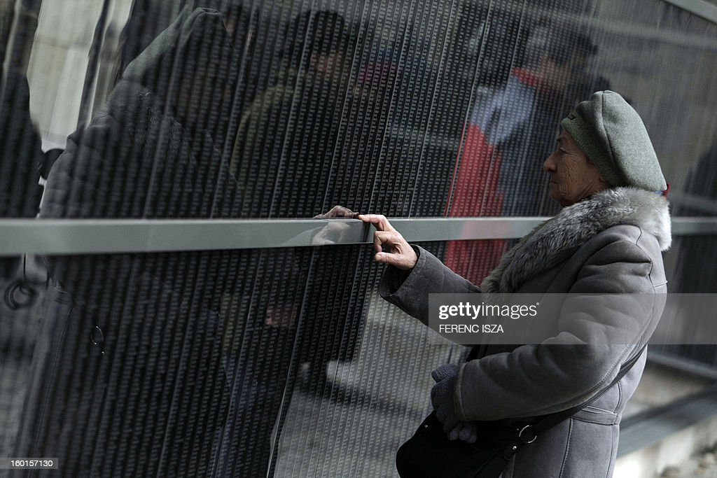 A Hungarian woman reacts as she stands in front of the wall of victims at the Holocaust Museum in Budapest on January 27, 2013, the International Holocaust Memorial Day to commemorate the victims of the Nazi regime.