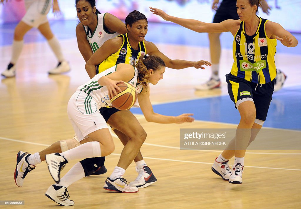 Hungarian Zsofia Somon (down) of Hungarian Hat-Agro UNI Gyor leads the ball against Latvian Ieva Kublina (R) and US Angel McCoughtry (L -up) of the Turkish Fenerbahce Istanbul in Gyor on February 22, 2013 during their EuroLeague match.