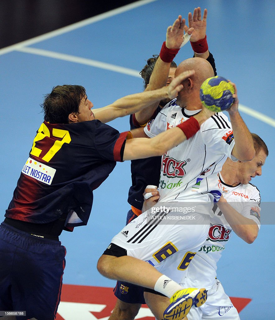 Hungarian Zsolt Balogh of PICK-Szeged is fouled by Spanish FC Barcelona's Viran Morros (L) on November 18, 2012 during their EHF Champions League match.