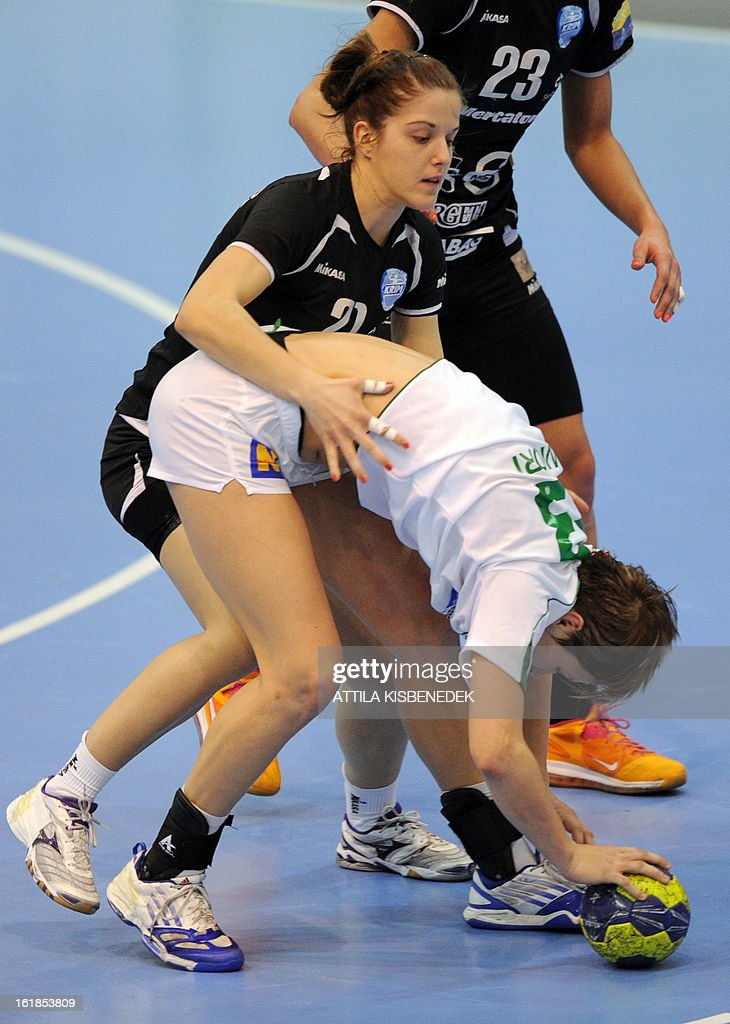 Hungarian Zsuzsanna Tomori (R) of FTC Rail Cargo Hungaria is pushed by Slovenian Alja Jankovic (L) of RK Krim Mercator in the local sports hall of Dabas on February 17, 2013 during their EHF Women's Champions League handball match. AFP PHOTO / ATTILA KISBENEDEK