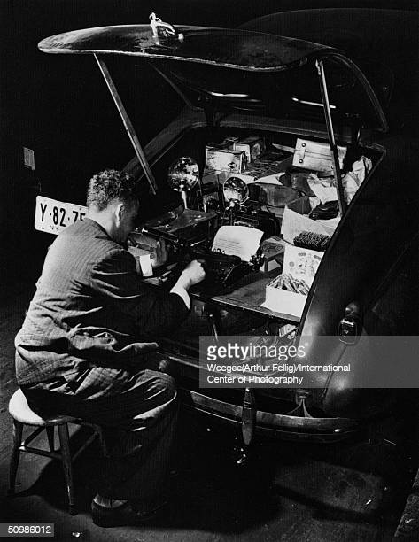 Hungarianborn photographer Weegee sits on a stool typing on a typewriter in the trunk of his Chevrolet automobile while smoking a cigar 1942