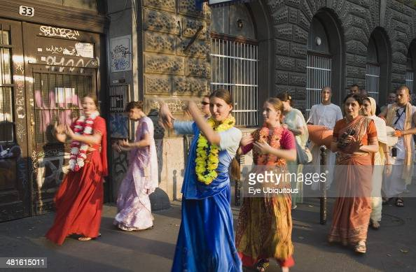 Hungary Pest County Budapest Hare Krishna devotees singing and dancing on Andrassy UtIn Pest with graffiti covered doorway behind The International...