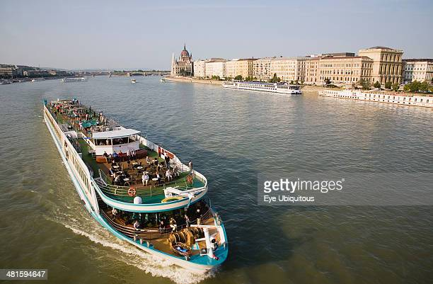Hungary Pest County Budapest Pleasure cruise boat on the River Danube approaching Szechenyi Chain Bridge or Memory Bridge with Hungarian Parliament...