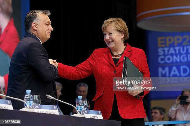Hungary Prime Minister Viktor Orban congratulates German Chancellor Angela Merkel as she arrives to the plenary session of the European People's...