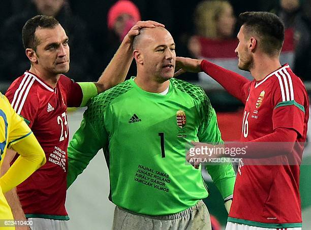 Hungary's 40year old goalkeeper Gabor Kiraly is welcomed by his teammates Roland Juhasz and Adam Pinter during the friendly football match between...