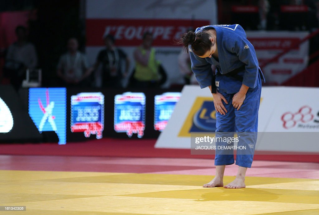Hungary's Abigel Joo back on the mat, salutes to apologise after leaving her fight against Japan's Sato Ruika on February 10, 2013 in Paris, during the Eliminatories of the Women -78kg of the Paris Judo Grand Slam tournament. AFP PHOTO/JACQUES DEMARTHON