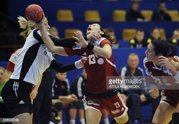 Hungary's Anita Görbicz is fouled by Russia's leftback Anna Sen during the 2012 EHF European Women's Handball Championship Group II match of main...