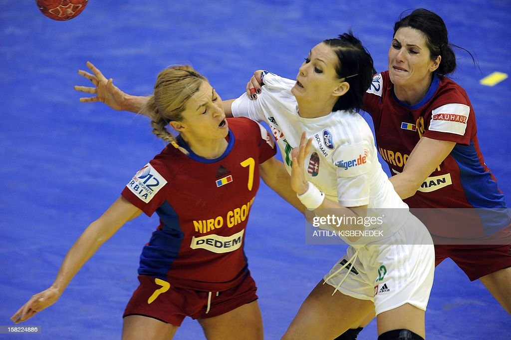 Hungary's Anita Görbicz (C) passes the ball between Romania's Adriana Nechita (L) and Romania's Cristina Neagu (R) during the 2012 EHF European Women's Handball Championship Group II match of the main round on December 11 , 2012, at the local arena of Novi Sad. Hungary won 25-19.