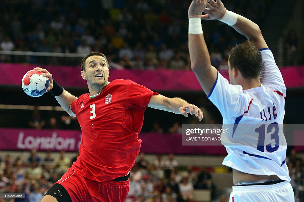 Hungary's back Ferenc Ilyes (L) tries to shoot in front of Serbia's Momir Ilic (R) during the men's preliminary Group B handball match Hungary vs Serbia for the London 2012 Olympics Games on August 6, 2012 at the Copper Box hall in London. AFP PHOTO/ JAVIER SORIANO