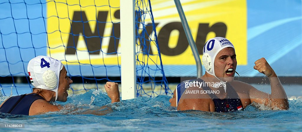Hungary's Barbara Bujka (R) and Dora Agnes Kisteleki (L) celebrate a goal during their preliminary round match Hungary vs Italy of the women's water polo competition at the FINA World Championships in Bernat Picornell pools in Barcelona on July 23, 2013. AFP PHOTO / JAVIER SORIANO
