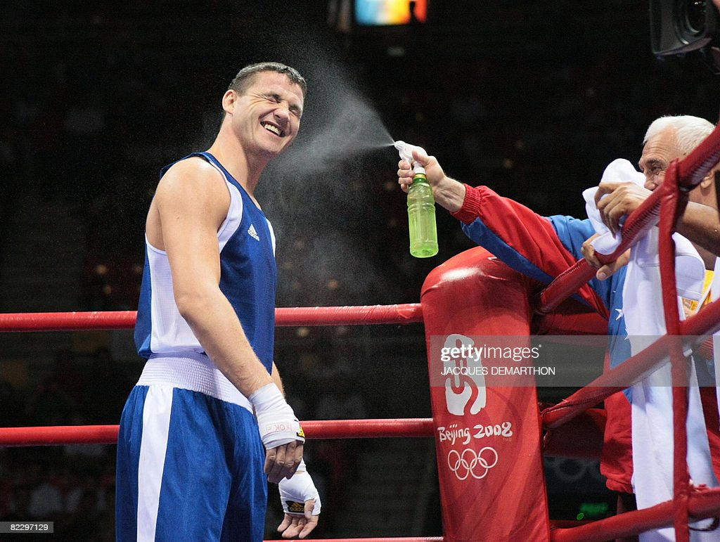 Hungary's Imre Szello is sprayed by his coach after being declared winner defeating Venezuela's Luis Gonzalez during their 2008 Olympic Games Light...