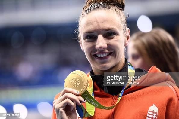 Hungary's Katinka Hosszu poses with her gold medal on the podium after she won the Women's 100m Backstroke Final during the swimming event at the Rio...