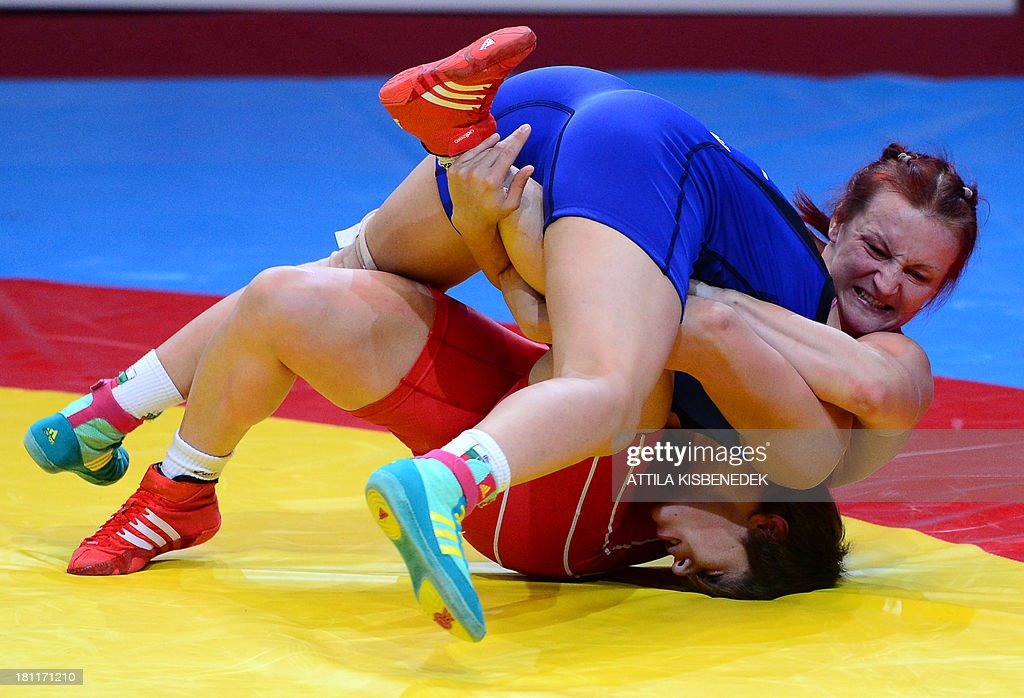 Hungary's Marianna Sastin (red) fights with Bulgaria's Taybe Mustafa Yusein (blue) during the women's free style 59 kg category final of the FILA World Wrestling Championships in Budapest on September 19, 2013. Sastin won the gold medal.