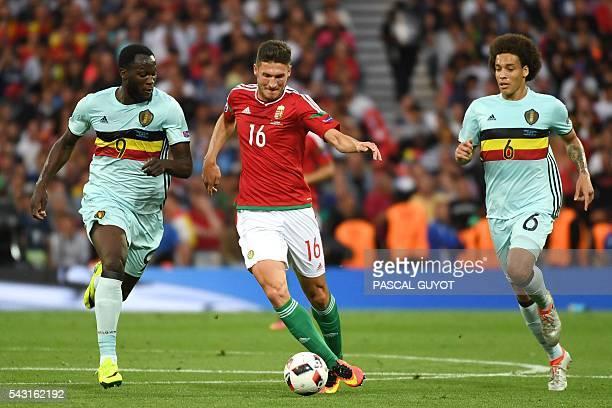 Hungary's midfielder Adam Pinter runs with the ball next to Belgium's forward Romelu Lukaku and Belgium's midfielder Axel Witsel during the Euro 2016...