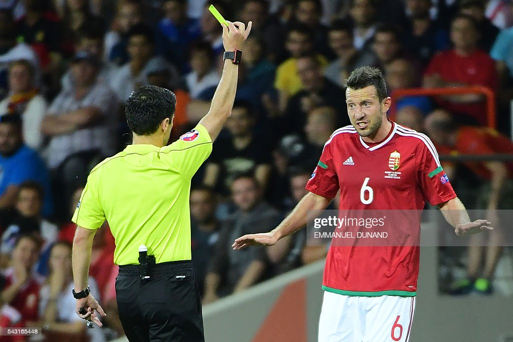 Hungary's midfielder Akos Elek (R) reacts as he receives a yellow card from Serbian referee Milorad Mazic during the Euro 2016 round of 16 football match between Hungary and Belgium at the Stadium Municipal in Toulouse on June 26, 2016. / AFP / EMMANUEL