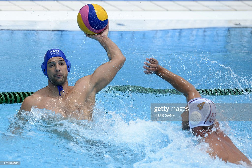 Hungary's Norbet Madaras (L) vies with Serbia's Vanja Udovicic (R) during the preliminary round match of the men's water polo competition between Serbia and Hungary at the FINA World Championships at the Bernat Picornell swimming pool in Barcelona on July 24, 2013. AFP PHOTO / LLUIS GENE