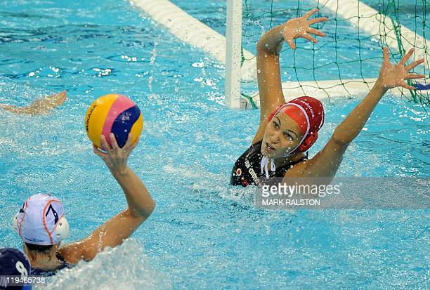 Hungary's Orsolya Kaso jumps to catch a shot from Netherlands's Lefke Van Belkum during the women's group A water polo preliminary round match in the...