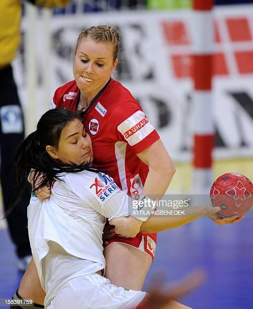 Hungary's Orsolya Verten is fouled by Norway's Karoline Dyhre Breivang during the 2012 EHF European Women's Handball Championship semifinal match...
