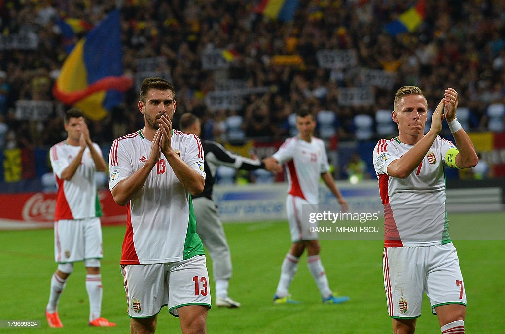 Hungary's player Daniel Bode (L) and Hungary's player Balazs Dzsudzsak react at the final whistle of the FIFA World Cup 2014 group D qualifying football match Romania vs Hungary on September 6, 2013 in Bucharest, Romania. Romania won 3-0.