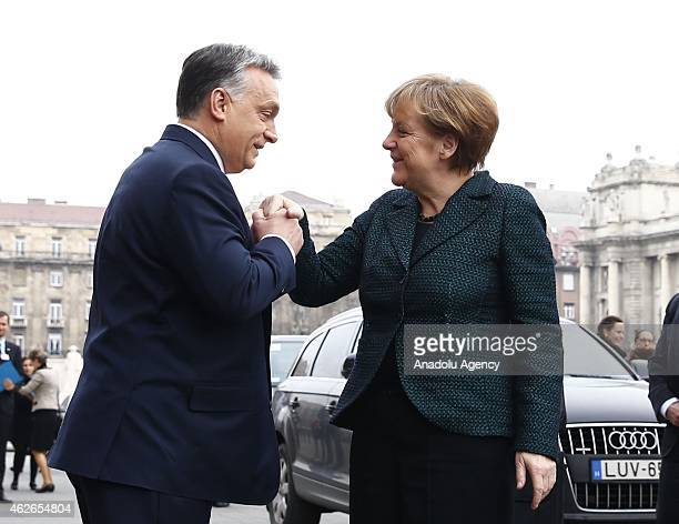 Hungary's prime minister Viktor Orban welcomes German Chancellor Angela Merkel during Merkel's official visit in front of the Parliament building in...
