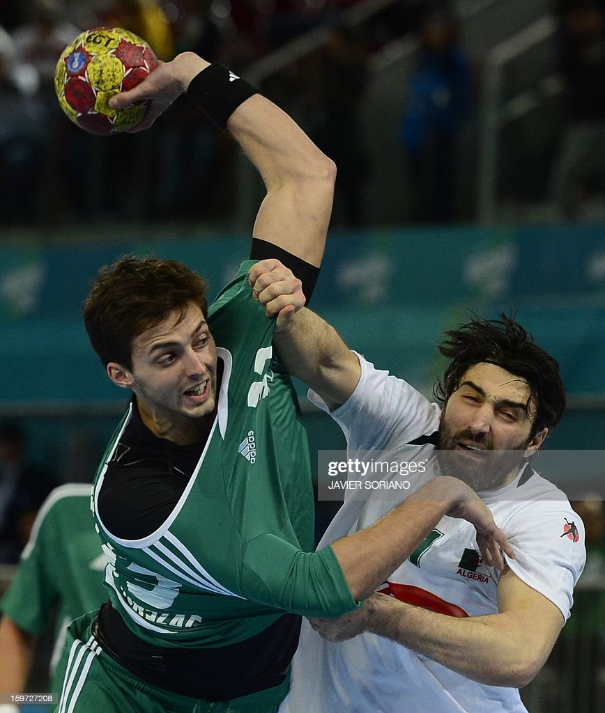 Hungary's right back Gabor Ancsin (L) vies with Algeria's pivot Mohamed Aski Mokrani during the 23rd Men's Handball World Championships preliminary round Group D match Hungary vs Algeria at the Caja Magica in Madrid on January 19, 2013.