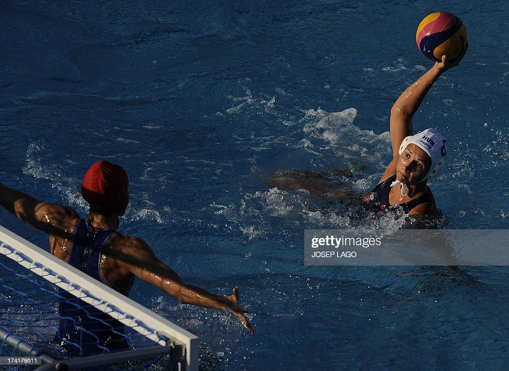 Hungary's Rita Keszthelyi (R) scores against Brazil's Manuela Canetti (L) during the preliminary rounds of the women's water polo at the FINA World Championships on July 21, 2013 at the Bernat Picornell swimming pool in Barcelona. Hungary won the match 20-6.