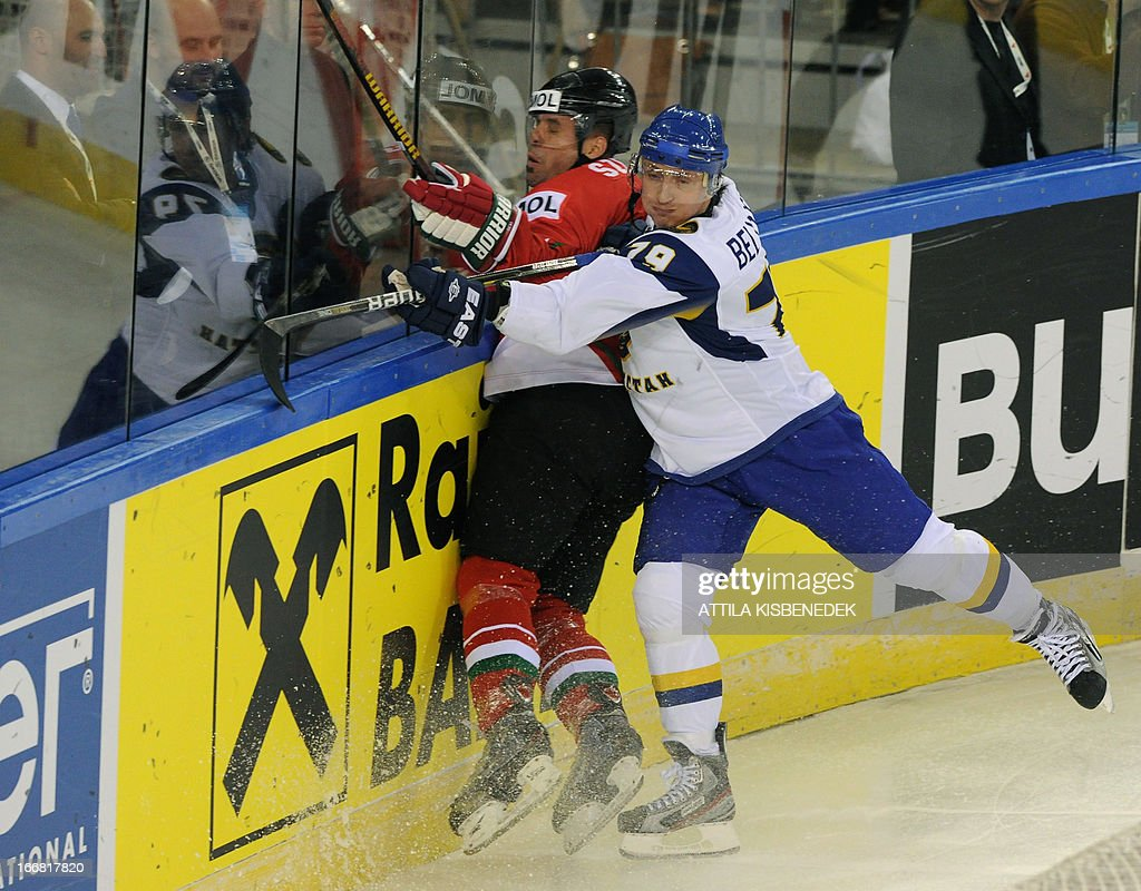Hungary's Viktor Szelig (L) is pushed by Kazakhstan's Maxim Belyayev (R) during the 2013 IIHF Ice Hockey World Championship Division I Group A match Kazakhstan vs Hungary in 'Papp Laszlo' Arena of Budapest on April 17, 2013.