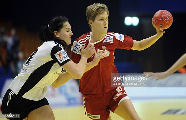 Hungary's Zsuzsanna Tomori is pushed by Russia's rightback Anna Punko during the 2012 EHF European Women's Handball Championship Group II match of...