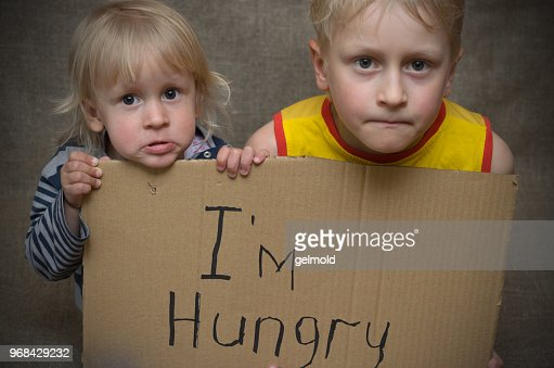 A hungry boy and a girl with a cardboard tablet with the inscription I'm hungry . : Stock Photo