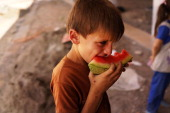 A hungry child eats a piece of watermellon in an empty store at a construction site where he is living with dozens of other displaced Iraqis who have...
