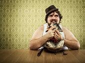 hungry fat man licking fish head soup at wood table